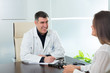 Doctor man and patient woman on hospital office talking