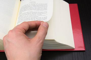 Hand blättert in einem Buch Arbeitsrecht