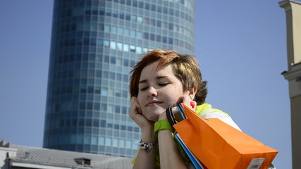 Young woman with shopping on the background of a skyscraper