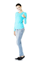 Young woman in casual clothes gesturing thumb up.