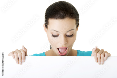 Shocked woman holding blank board