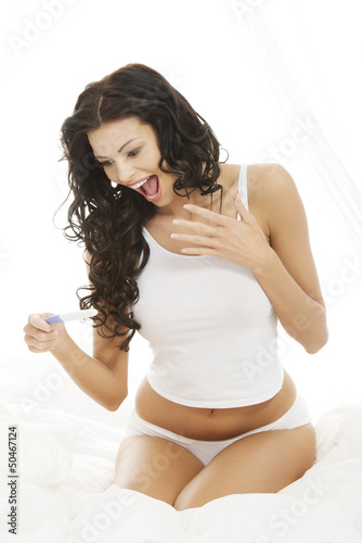 Happy woman on bed with pregnancy test