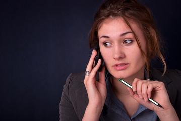 Kobieta z długopisem i telefonem przy uchu