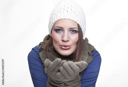 Beautiful woman in winter outfit blowing wind