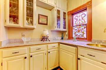 White kitchen pantry with antique cabinets and window.