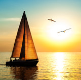 Yacht sailing against sunset with seagulls