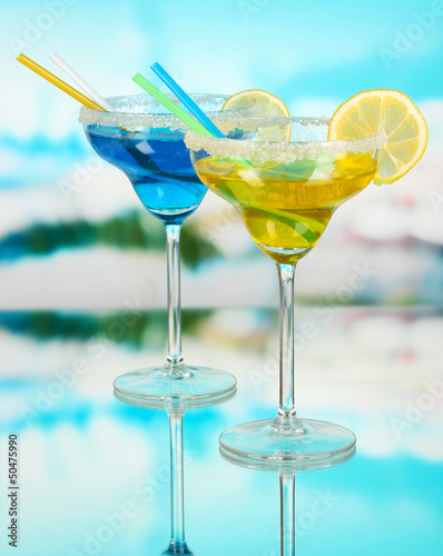 Yellow and blue cocktails in glasses on blue natural background