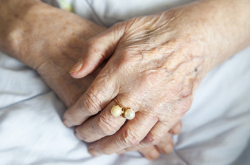 Hands of elderly lady with golden ring-series of photos