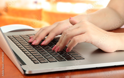 Female hands writing on laptop, on bright background