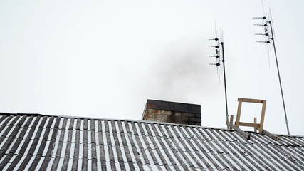 old house slate roof snow dark smoke rise chimney antenna winter