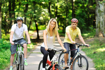 Portrait of attractive young woman on bicycle and two men in blu