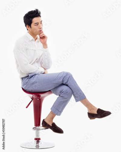 Young Asian man thinking on the chair.