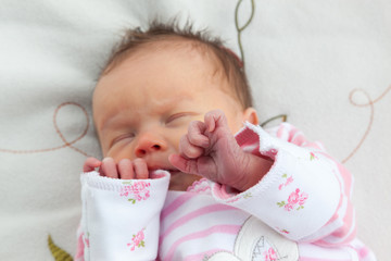 Newborn baby girl clutching her hands to her face