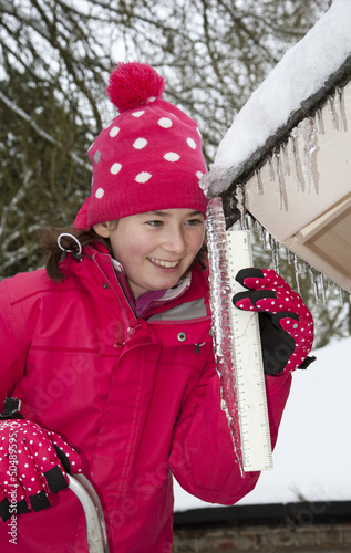 Young girl checks the size of an icicle with a ruler