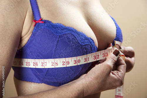 Woman using a tape measure to check bra size