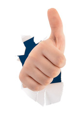 Child hand making thumbs up sign breaking through paper