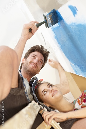 Happy couple painting wall