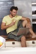 Young man with laptop in kitchen