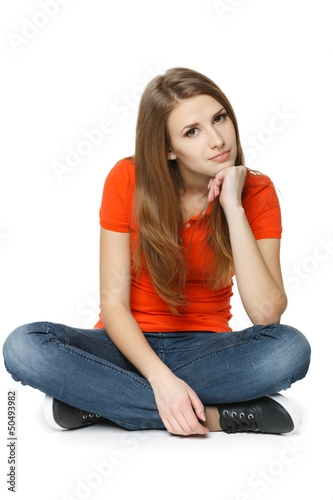 Calm woman sitting on the floor with chin on hand