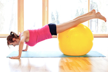 Young fit woman with fitness ball