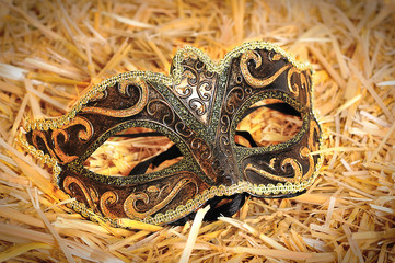 Venetian Carnival mask decorated with golden ornament on the hea