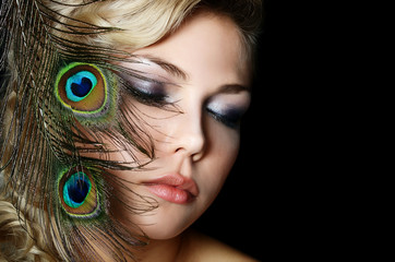 The beautiful woman with feathers of a peacock