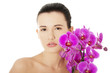 Young woman with health skin and with orchid flower