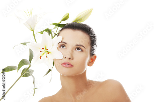 Young woman with health skin and with lily flower