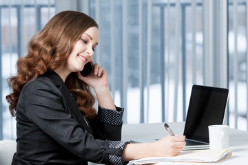 Business woman at office desk talking on telephone.