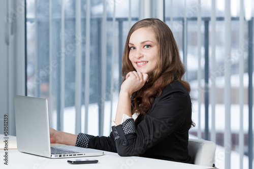 Portrait of a  business woman at office desk and laptop.