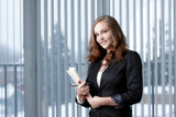 Business woman holding documents in modern office.