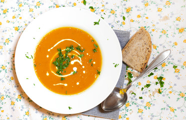 Carrot soup with cream and parsley, bread slice