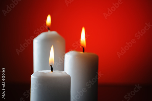Three candles on red background