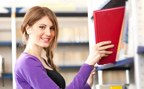 Young student taking a book in a library