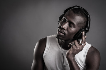 African man with ear-phones isolated on dark background.