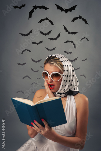 Scared retro woman reading book with bats silhouettes