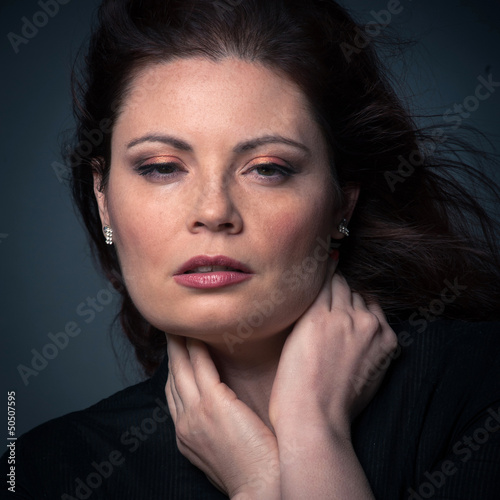 Sensual red head woman close up portrait on dark background.