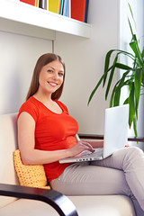 smiley woman with laptop at home