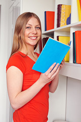 woman holding book and looking at camera