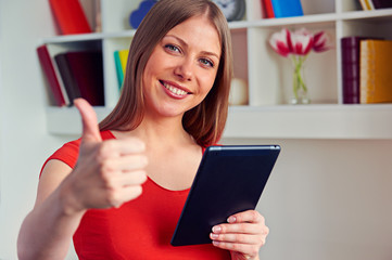 woman holding tablet pc and showing thumbs up