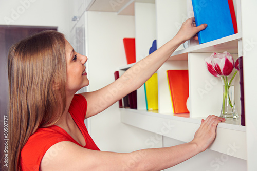 woman getting book from the shelf