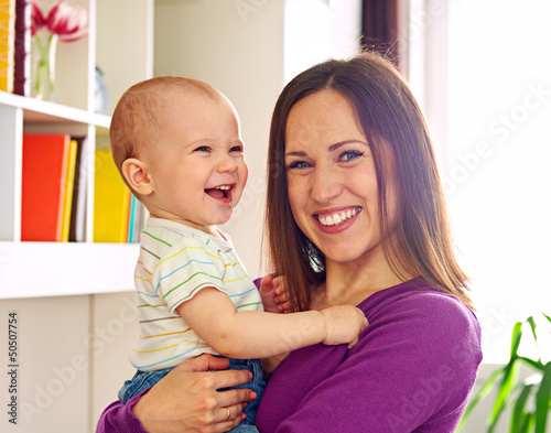 smiley mother and adorable son at home