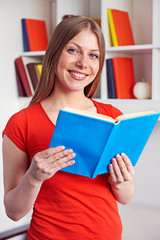 young woman holding the book and smiling