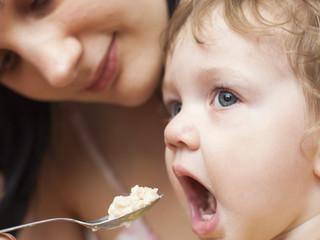Мама кормит маленького ребенка кашей с ложечки