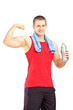 Athletic young male in sportswear showing his muscles and holdin