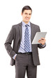 Smiling businessman holding a tablet