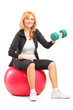 Smiling woman exercising with a dumbbell and sitting on a fitnes