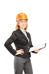 Female engineer with a helmet holding a clipboard and posing