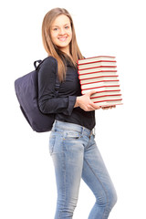 Female student with backpack holding a pile of books