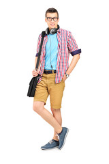 Full length portrait of a male student with a shoulder bag and h
